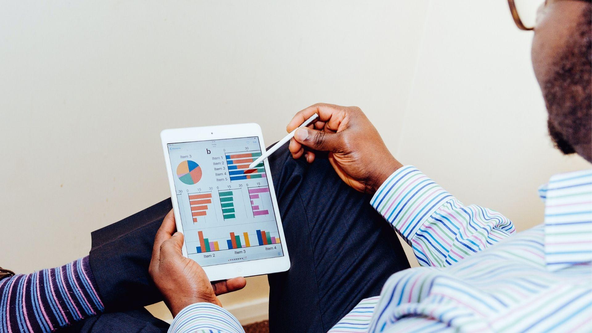 Un homme montre des graphiques sur un ipad.