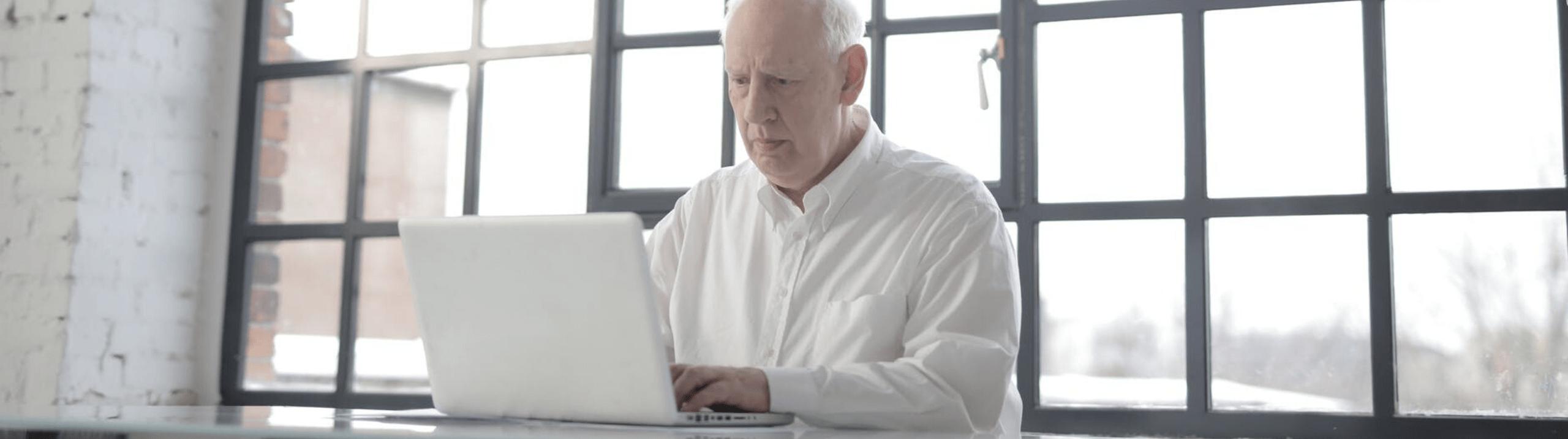 Un homme âgé assis devant un ordinateur.
