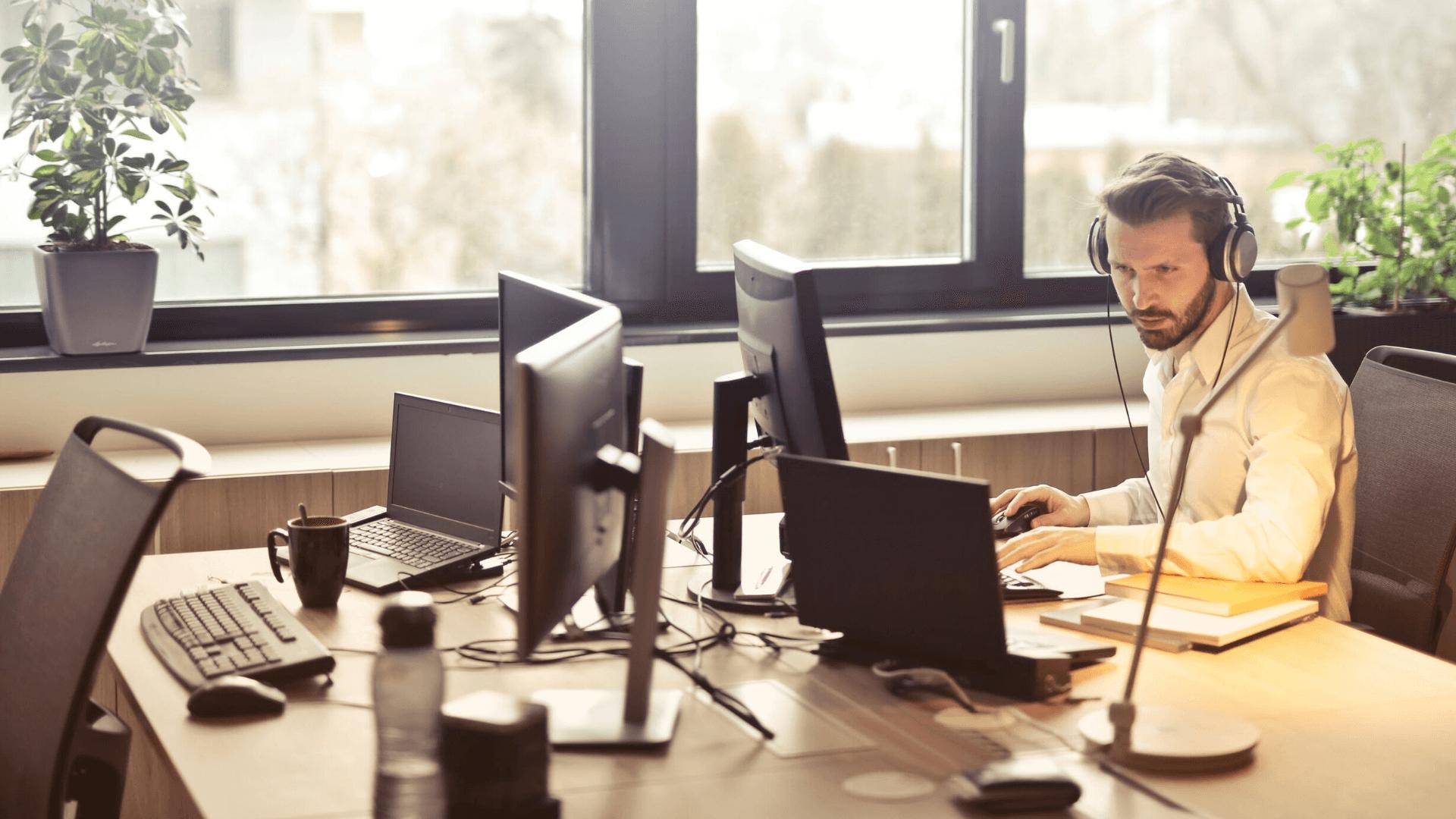 Un homme portant des écouteurs devant un ordinateur.