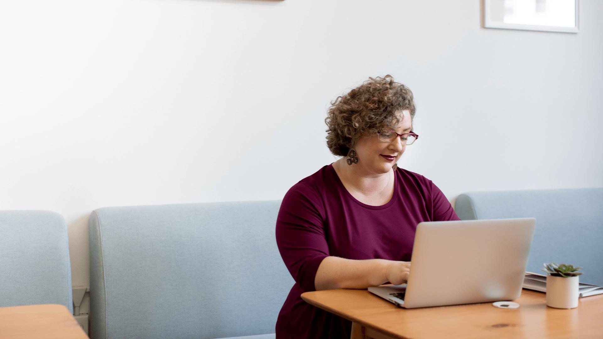 Une femme assise devant un ordinateur.