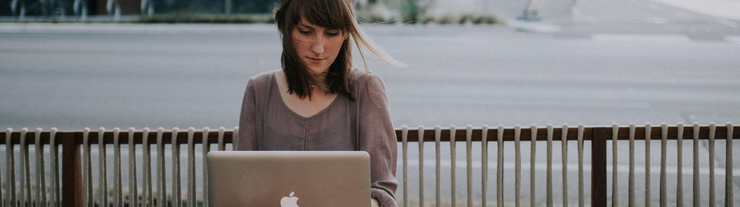 Une femme assise devant un ordinateur à l'extérieur devant une rue déserte.