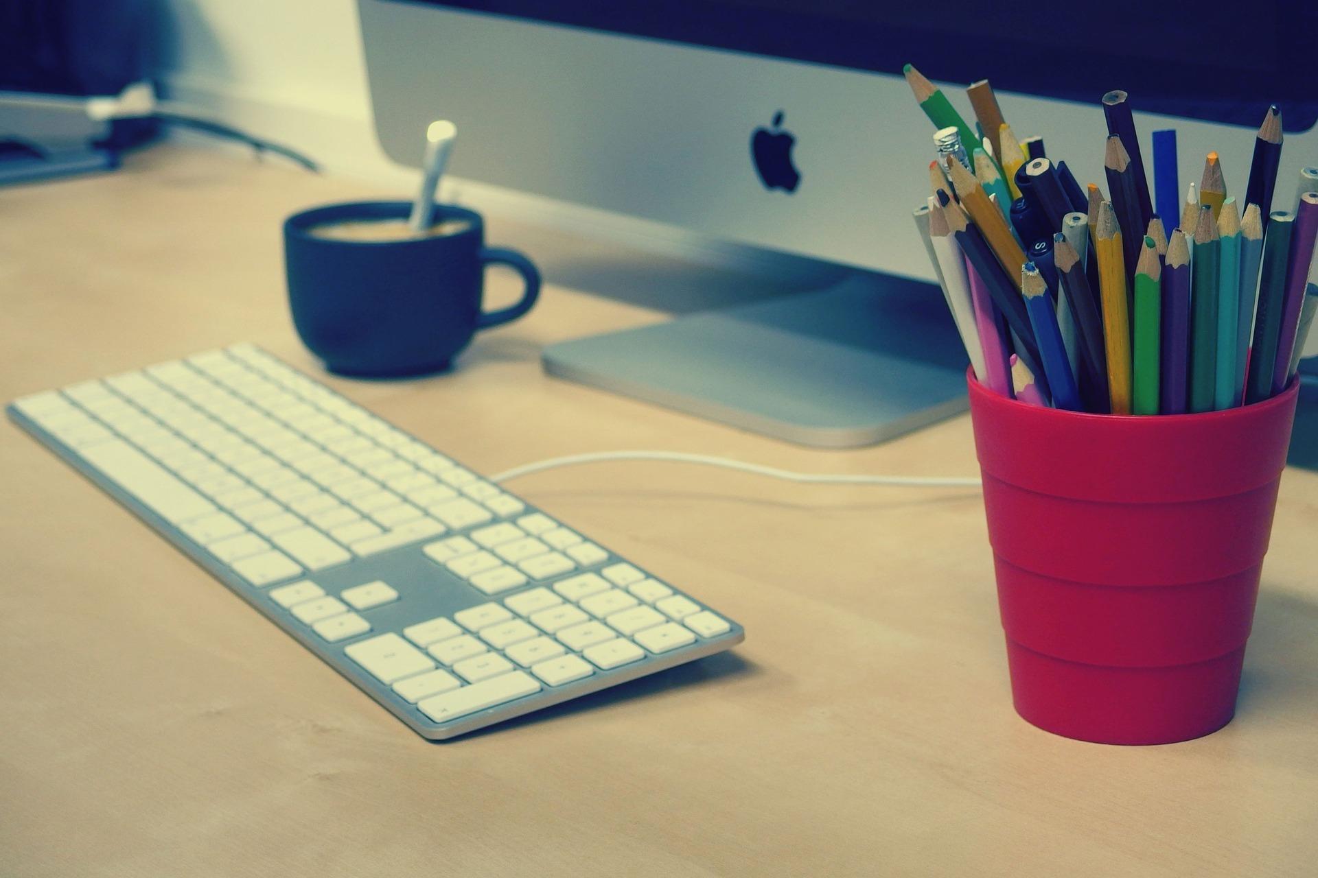Un ordinateur avec un pot de crayons de couleur.