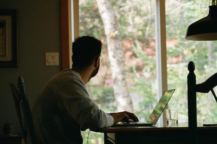Un homme assis devant son ordinateur regarde par la fenêtre.