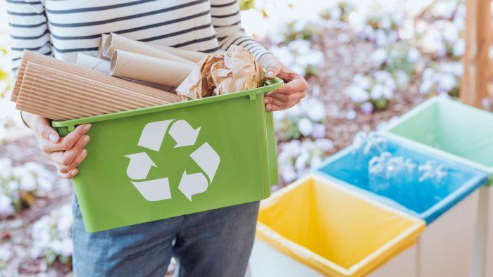 Une personne tenant un bac de recyclage.